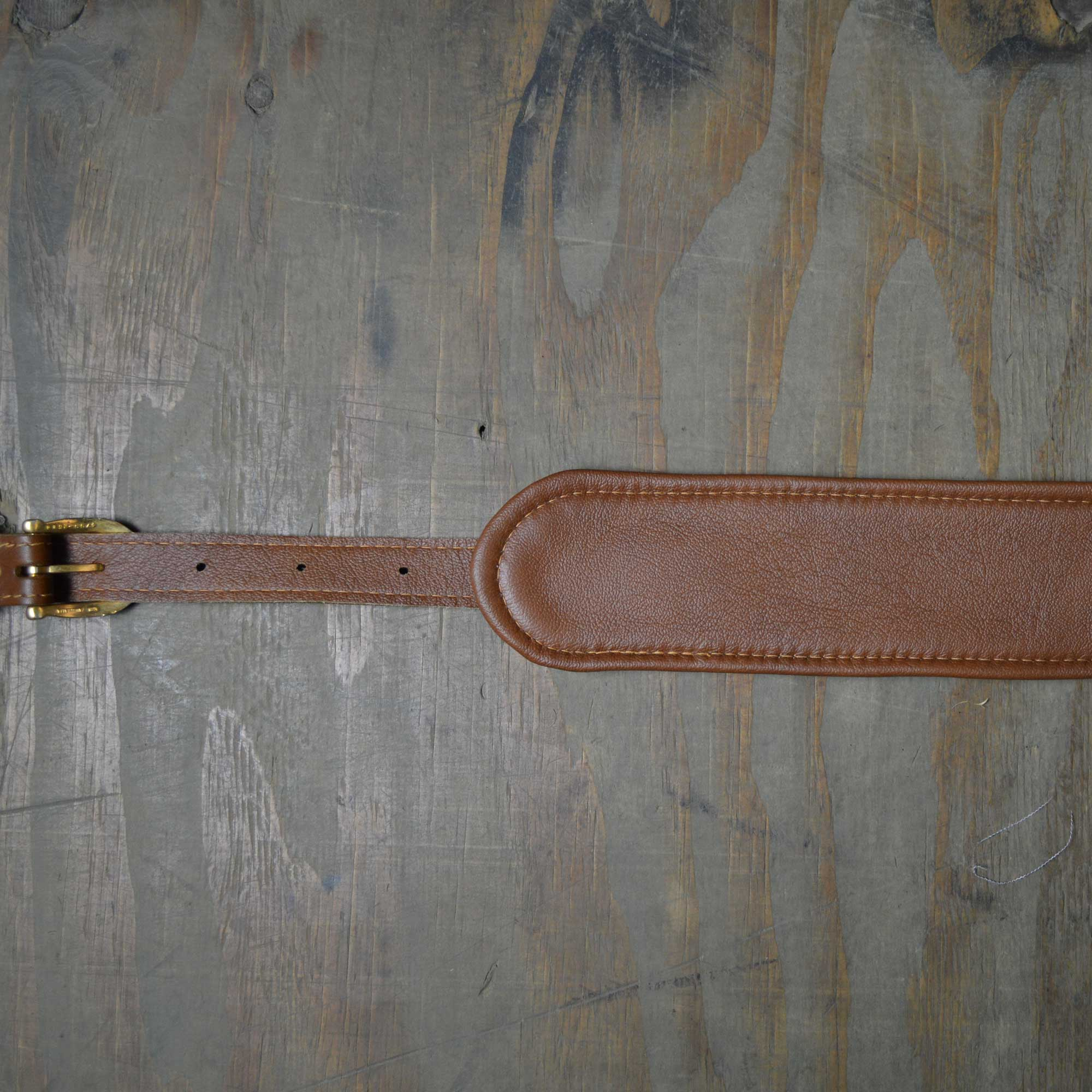 Vintage style guitar strap made with a topgrain leather top and an upholstery backing. Brown & Tan